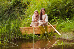 Cute little girls having fun in a boat by a river Stock Image