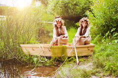 Cute little girls having fun in a boat by a river Royalty Free Stock Image