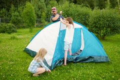 Cute little girls helping their parent to set up a tent on a campsite. Active lifestyle, family recreational weekend royalty free stock images