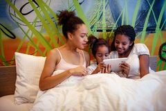 Cute little girls and her mother lying on a bed stock photos