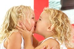 Cute little girls kissing each other at home. Close up portrait of cute little girls kissing each other at home Stock Photography
