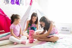 Girls Making Tower Of Pink Wooden Blocks During Pajama Party. Cute little girls making tower of pink wooden blocks during pajama party at home royalty free stock images