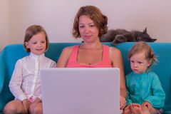 Cute little girls with mom watching the laptop. Stock Photography