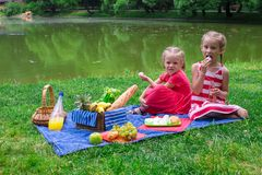 Cute little girls picnicing in the park at sunny Stock Images