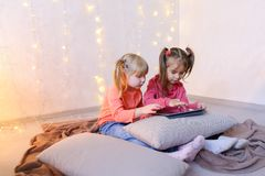 Little girls involved in use of tablet and sit on floor in brigh. Cute little girls play in computer games on device or watch cartoons, press something on touch Stock Photography