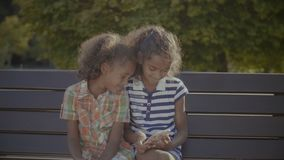Cute little girls playing online games on cellphone. Happy elementary age curly african american girls playing online games on smart phone while sitting on the stock footage