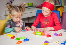 Cute little girls playing with plasticine. At home Royalty Free Stock Image