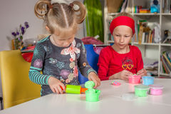 Cute little girls playing with plasticine. At home Stock Photos