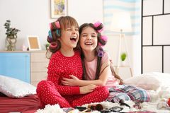 Cute little girls playing with their mother`s stuff. On bed royalty free stock image