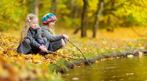 Cute little girls playing by the water on beautiful autumn day. Happy children having fun in autumn park. Royalty Free Stock Image