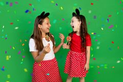 Cute little girls in red outfits on a green isolated background eat large lollipops. Space for text. the concept of the