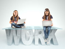 Cute little girls sitting on a WORK table design, and holding a laptop. Bussines concept Stock Image