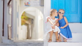 Cute little girls at street of typical greek traditional village with white walls and colorful doors on Mykonos Island stock video footage