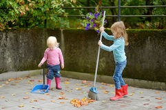 Cute little girls sweeping dry leaves on autumn stock photography