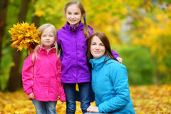 Cute little girls and their mother having fun on beautiful autumn day. Happy children playing in autumn park. Kids gathering yello. Two cute little girls and Stock Photo