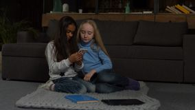Cute little girls typing message on smart phone. Happy little multiracial girlfriends surfing net with smart phone while sitting on the floor in home interior stock video footage