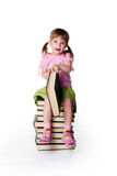 Cute little girlsit near a big books Royalty Free Stock Images