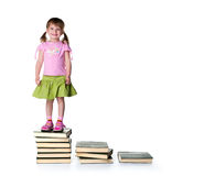 Cute little girlsit near a big books Stock Photos
