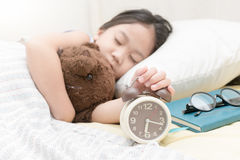 Cute little hand girl reaching to turn off alarm clock stock images