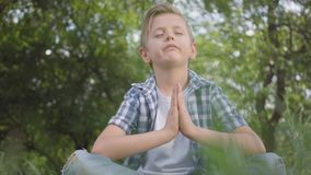 Cute little handsome boy sitting on the grass meditating. Child practices yoga. The spiritual development of kids. Summertime leisure stock video