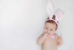 Cute little happy baby boy with rabbit's ears lying on soft whit Royalty Free Stock Images