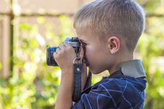 Cute little happy boy with vintage photo camera outdoors Stock Photos