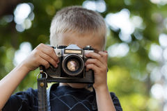 Cute little happy boy with vintage photo camera outdoors Royalty Free Stock Photography