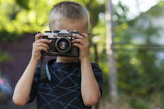 Cute little happy boy with vintage photo camera outdoors Royalty Free Stock Image