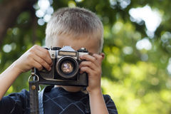 Cute little happy boy with vintage photo camera outdoors Royalty Free Stock Images