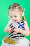 Cute Little smiling Girl holds Coins In Shopping basket Stock Images