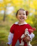 A cute little happy girl holding a teddy bear Stock Photo