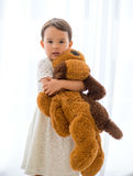 Cute little happy girl hugging big brown teddy bear Royalty Free Stock Photo