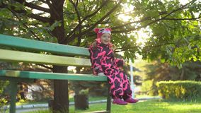 A cute little happy girl sits on a bench and swinging legs under an oak tree. Little sweet little happy girl in a warm pink overall sitting on a green bench and stock footage