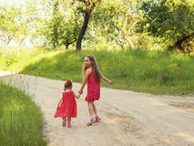 Cute little happy girls running in the green meadow at sunset Stock Images