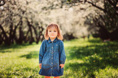 Cute little happy toddler girl portrait walking in spring or summer park. Or garden stock image