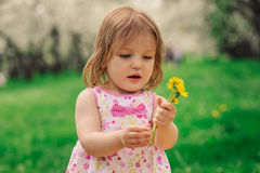 Cute little happy toddler girl portrait walking in spring or summer park. Or garden Stock Photography