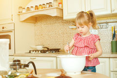 Cute little helper girl helping her mother cooking in a kitchen. Happy loving family are preparing bakery. Royalty Free Stock Images