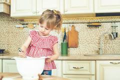 Cute little helper girl helping her mother cooking in a kitchen. Happy loving family are preparing bakery. Stock Photography