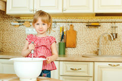 Cute little helper girl helping her mother cooking in a kitchen. Happy loving family are preparing bakery. Stock Photos