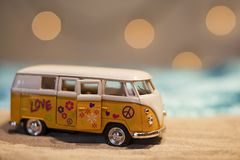 Cute yellow hippie van with peace sign on a sandy beach. Cute little hippie van with peace symbols on a sandy beach somewhere tropical Royalty Free Stock Photos