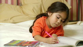 A cute little Hispanic child lying in bed coloring quietly stock video