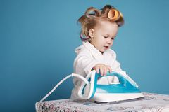 Cute little housewife with iron Royalty Free Stock Photography