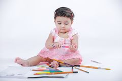 Cute little Indian/Asian Girl enjoying Painting  with paper, colour pencle and art brush.  royalty free stock image