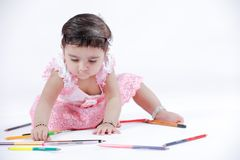 Cute little Indian/Asian Girl enjoying Painting  with paper, colour pencle and art brush.  stock image