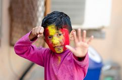 Cute Little Indian boy child with coloured face during holi indian festival looking at camera stock images