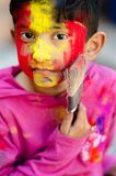 Cute Little Indian boy child with coloured face holding paint brush during holi indian festival looking at camera stock photography