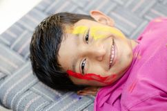 Cute Little Indian boy child with coloured face during holi indian festival looking at camera royalty free stock photos