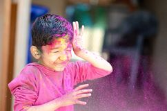 Cute Little Indian boy child with coloured face paint poweder color thrown at his face during holi indian festival looking at royalty free stock image