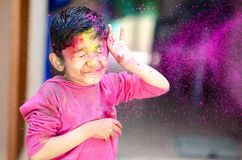 Cute Little Indian boy child with coloured paint thrown at face during holi indian festival looking at camera royalty free stock photo