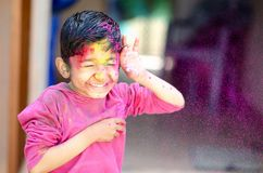 Cute Little Indian boy child with coloured face paint poweder color thrown at his face during holi indian festival looking at stock photos